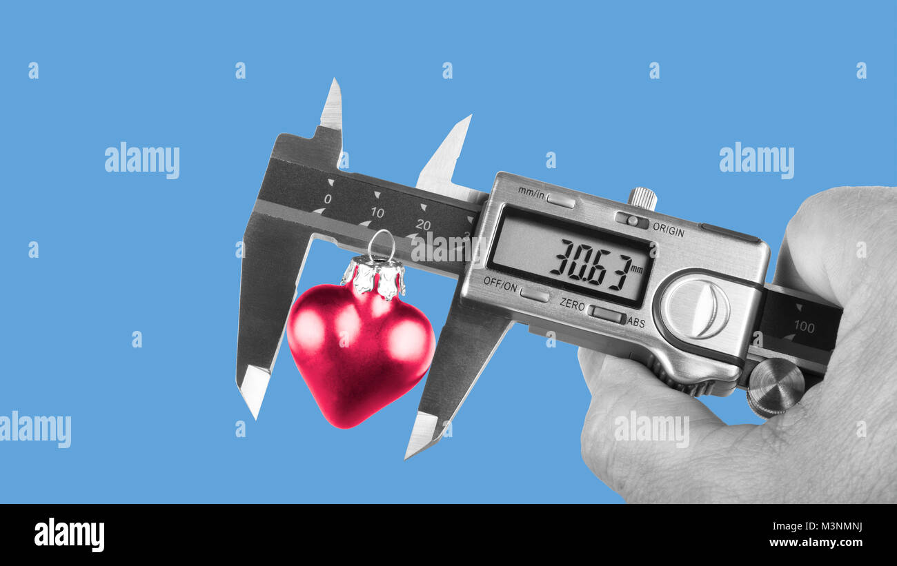 Black and white human hand holding caliper when measuring red heart. Size of love, relation to science or technology. - Stock Image