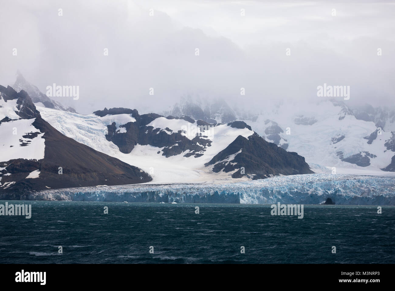 Big blue ice glacier against black mountains severe snow storm approaching over the mountain, Southern Ocean South Stock Photo