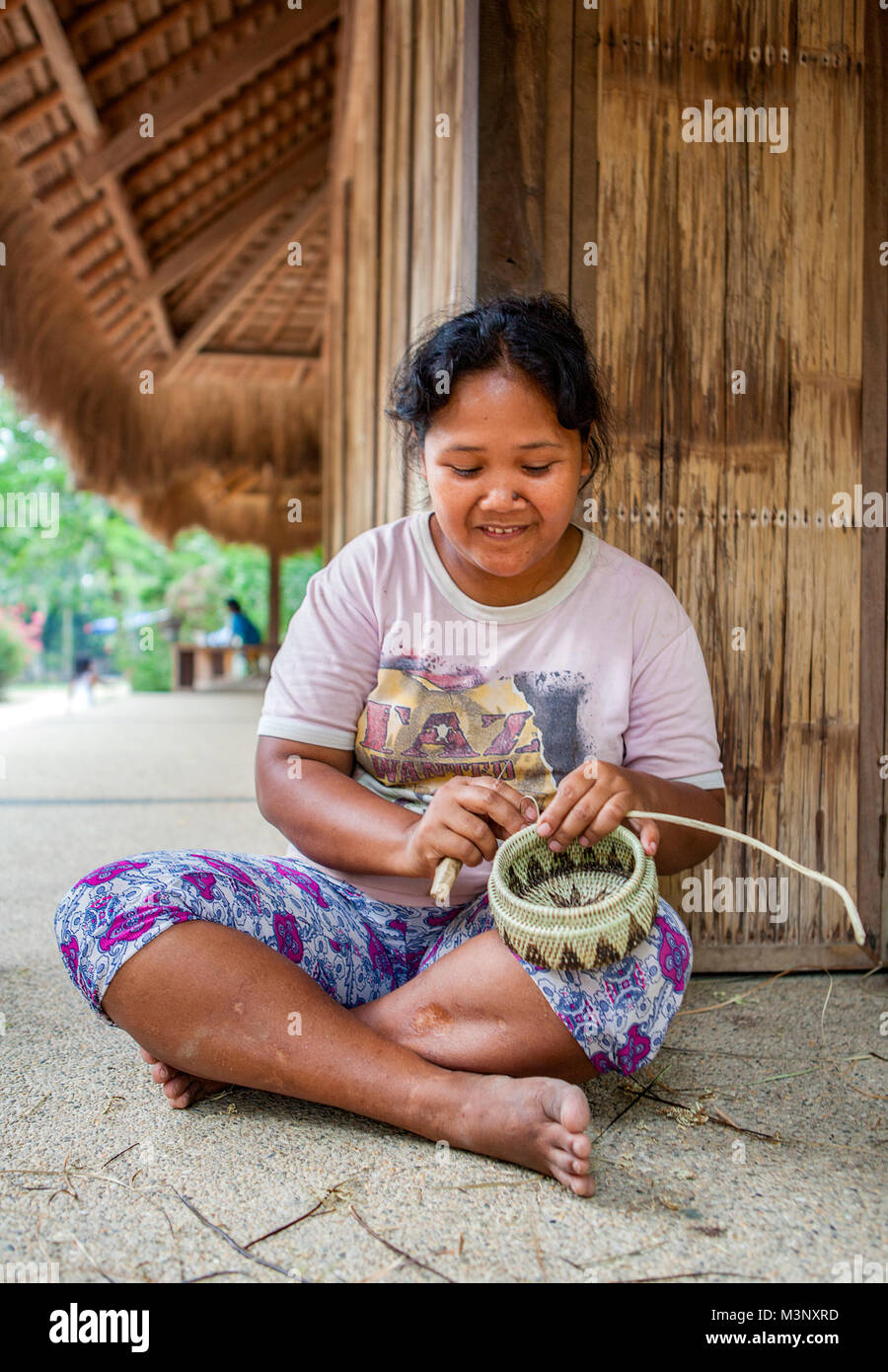 Aninuan, Oriental Mindoro, Philippines  -  A Mangyan craftswoman weaves a basket at her village of Sitio talipanan Stock Photo
