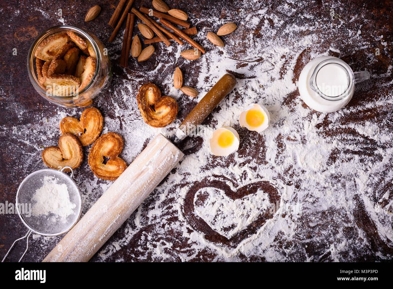 top view of tasty homemade cookies and ingredients on table top  - Stock Image