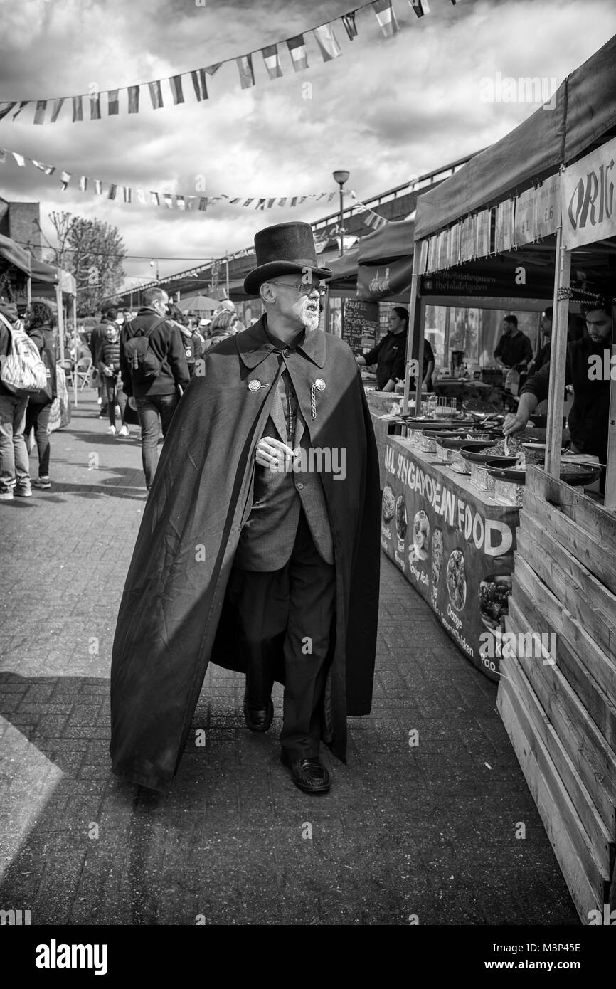 Black & White Photograph of an eccentric man in top hat and cape walking along Portobello Road, Notting Hill, - Stock Image
