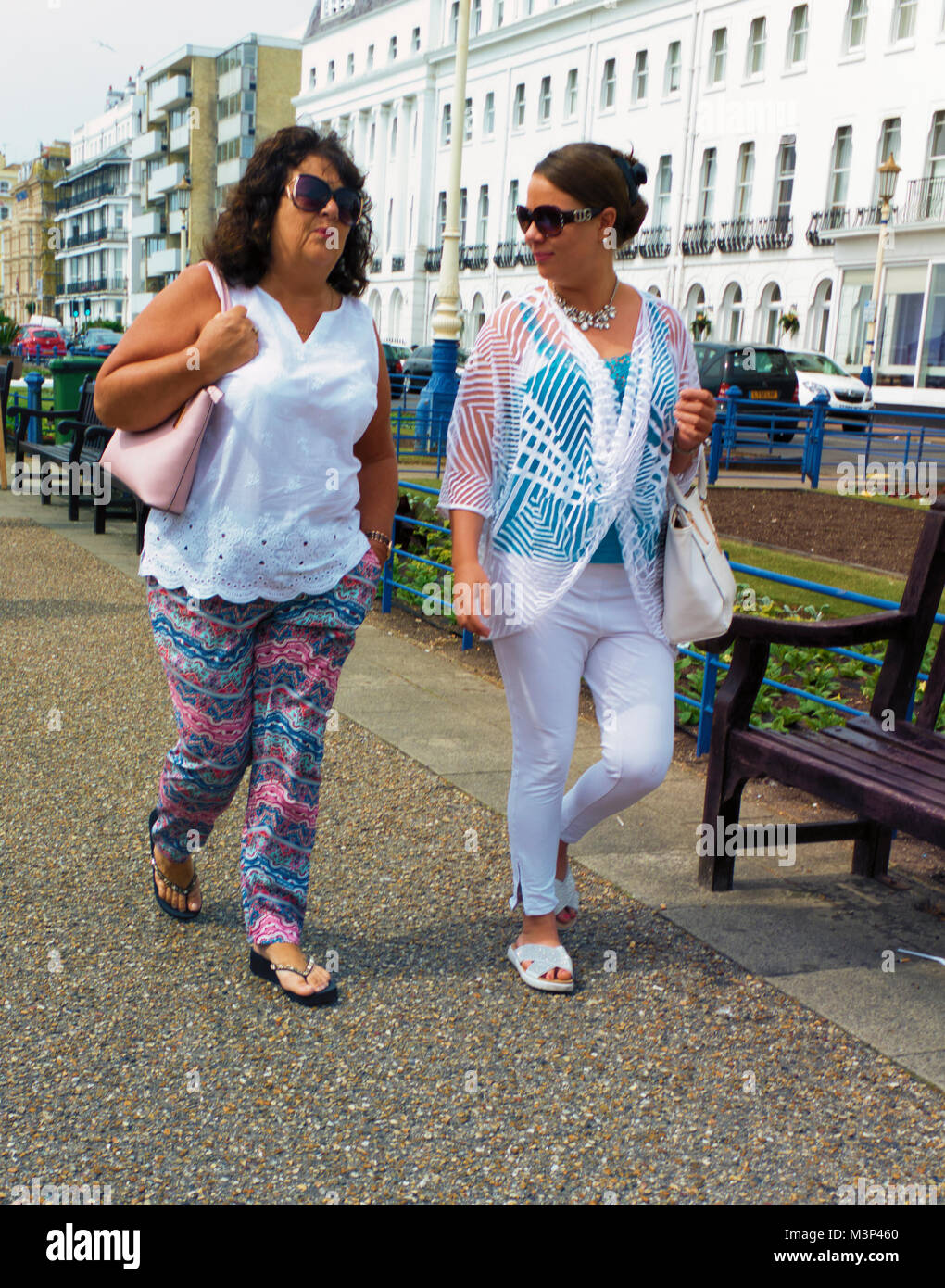 Colour Photograph of two Ladies taking a stroll along Worthing Sea Front in the spring time, Worthing, Sussex, England, - Stock Image