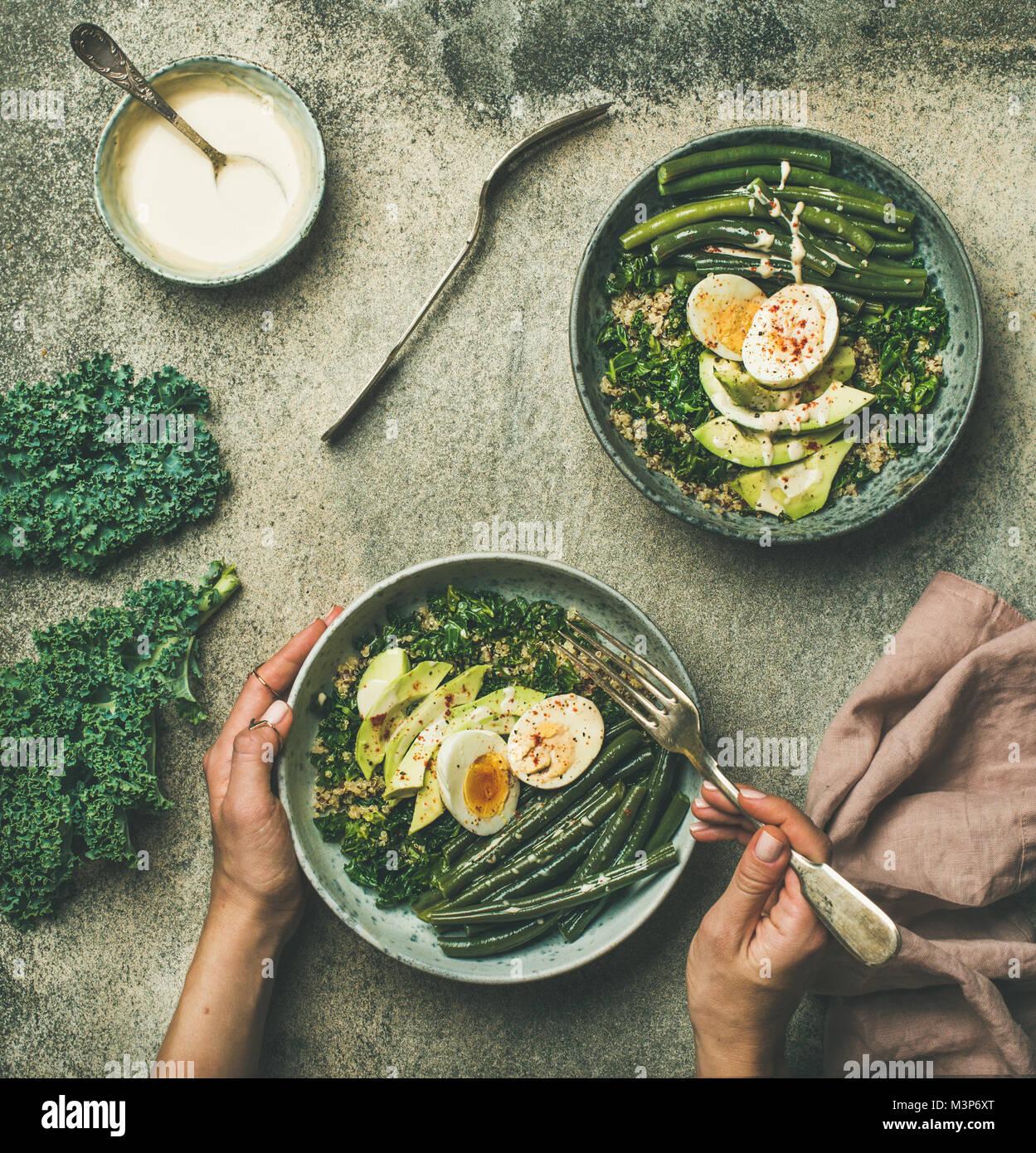 Quinoa, kale, beans, avocado, egg with creamy tahini dressing bowls - Stock Image
