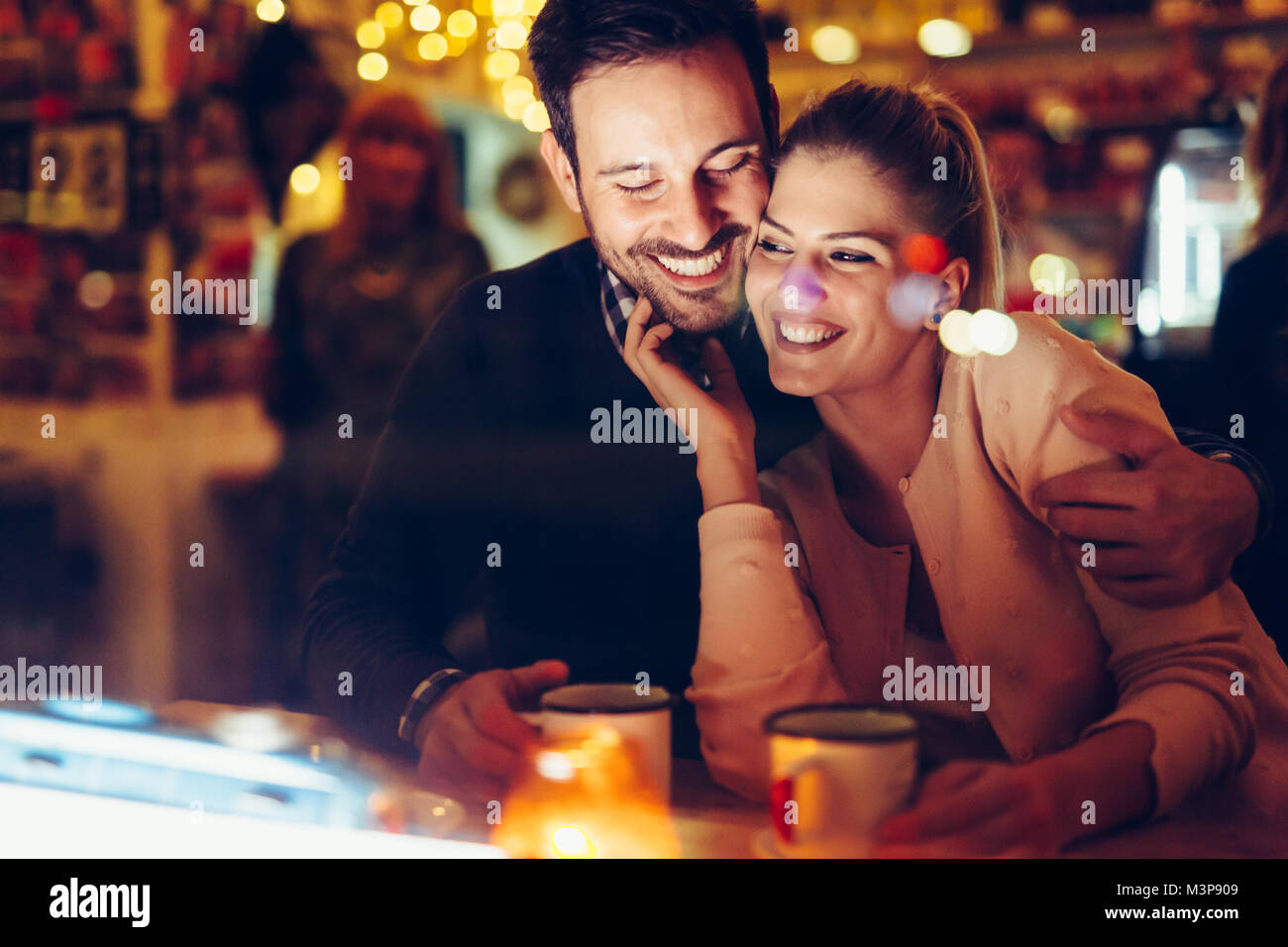 Romantic couple dating in pub at night - Stock Image