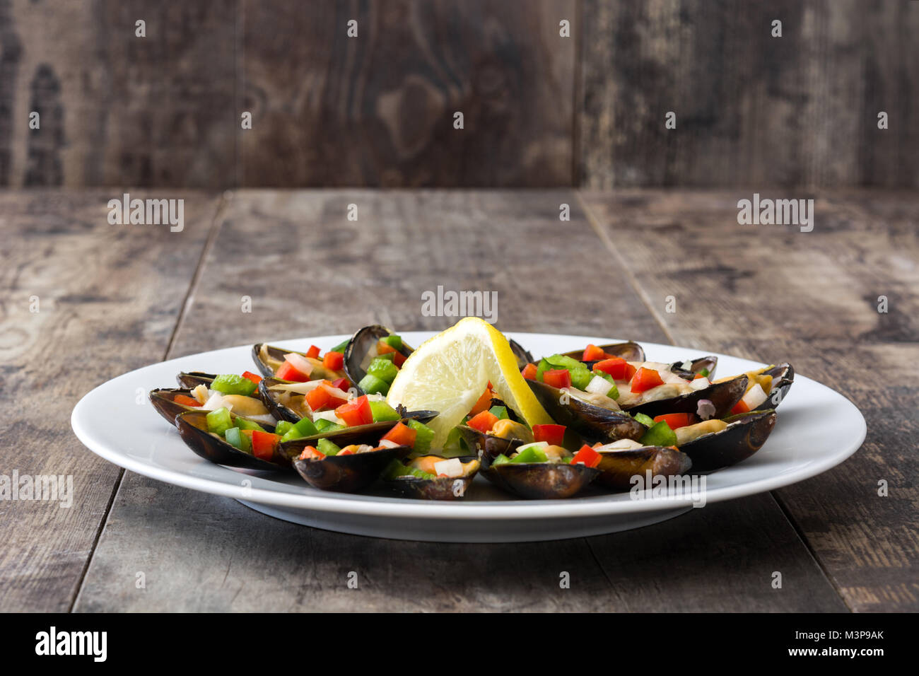 Steamed mussels with peppers and onion on wooden table Stock Photo