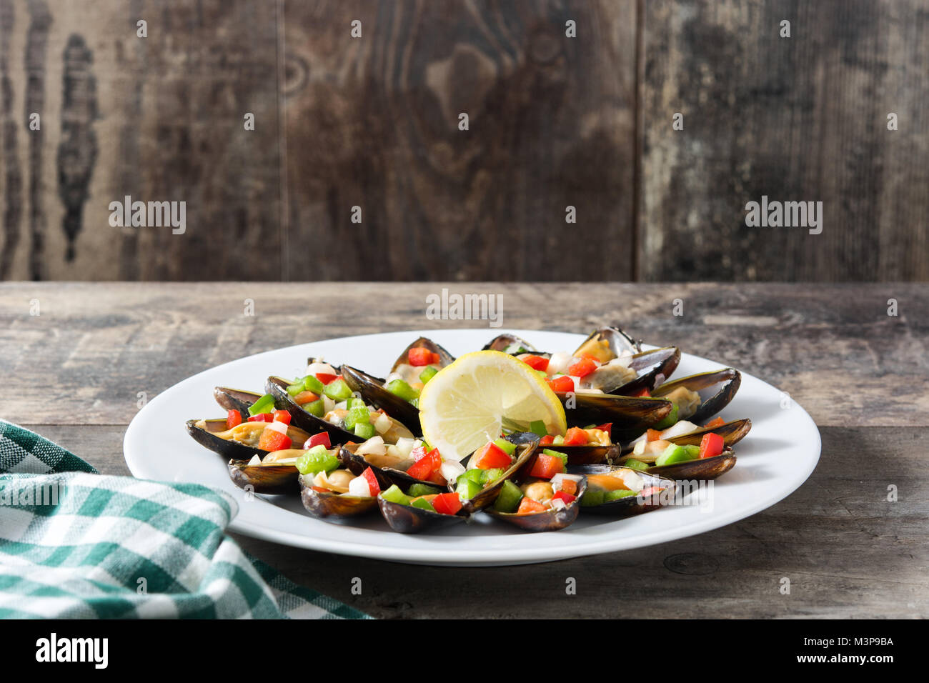 Steamed mussels with peppers and onion on wooden table - Stock Image