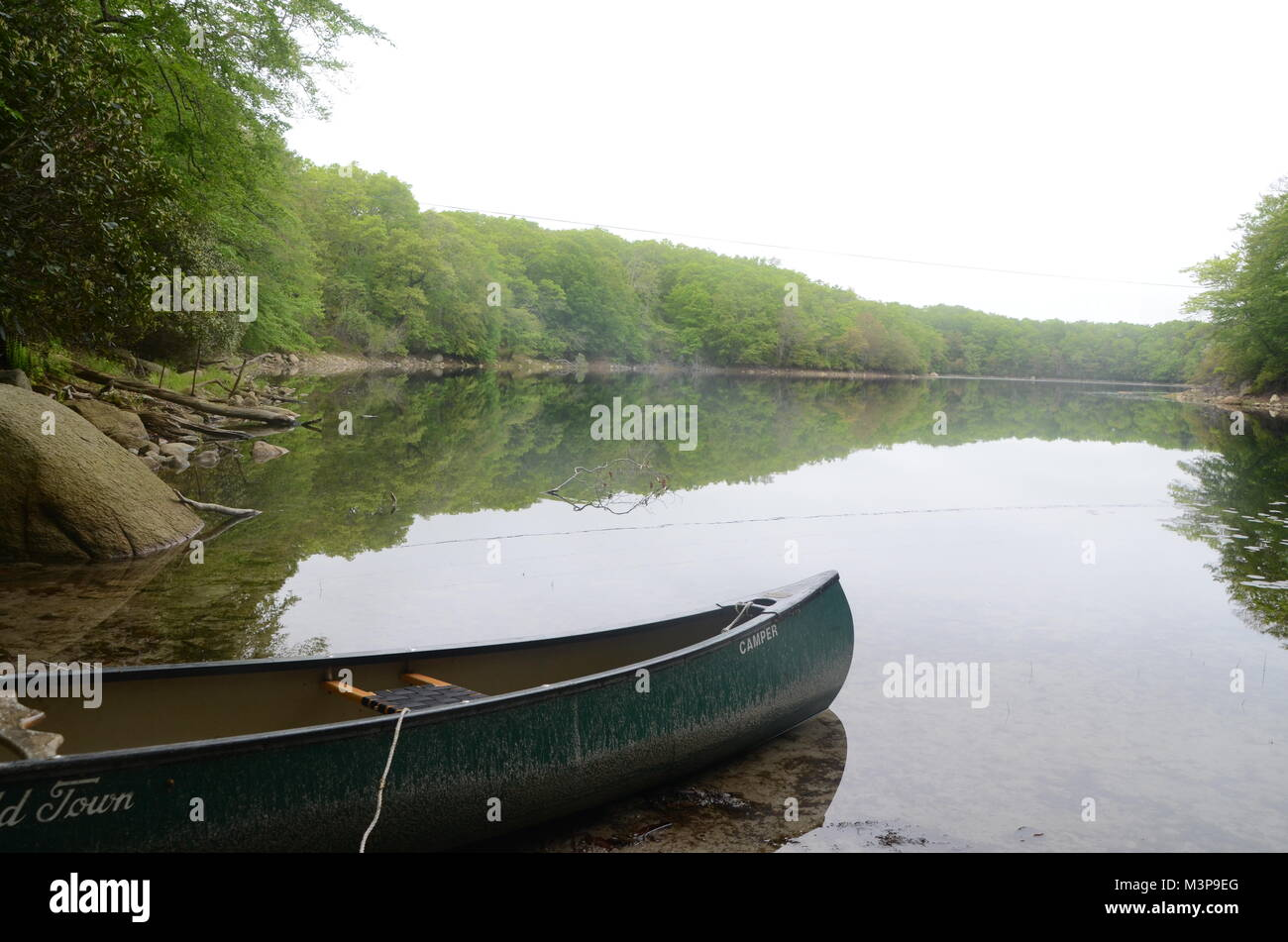 a green canoe on hothouse pond wakefeld south kingston rhode island USA Stock Photo