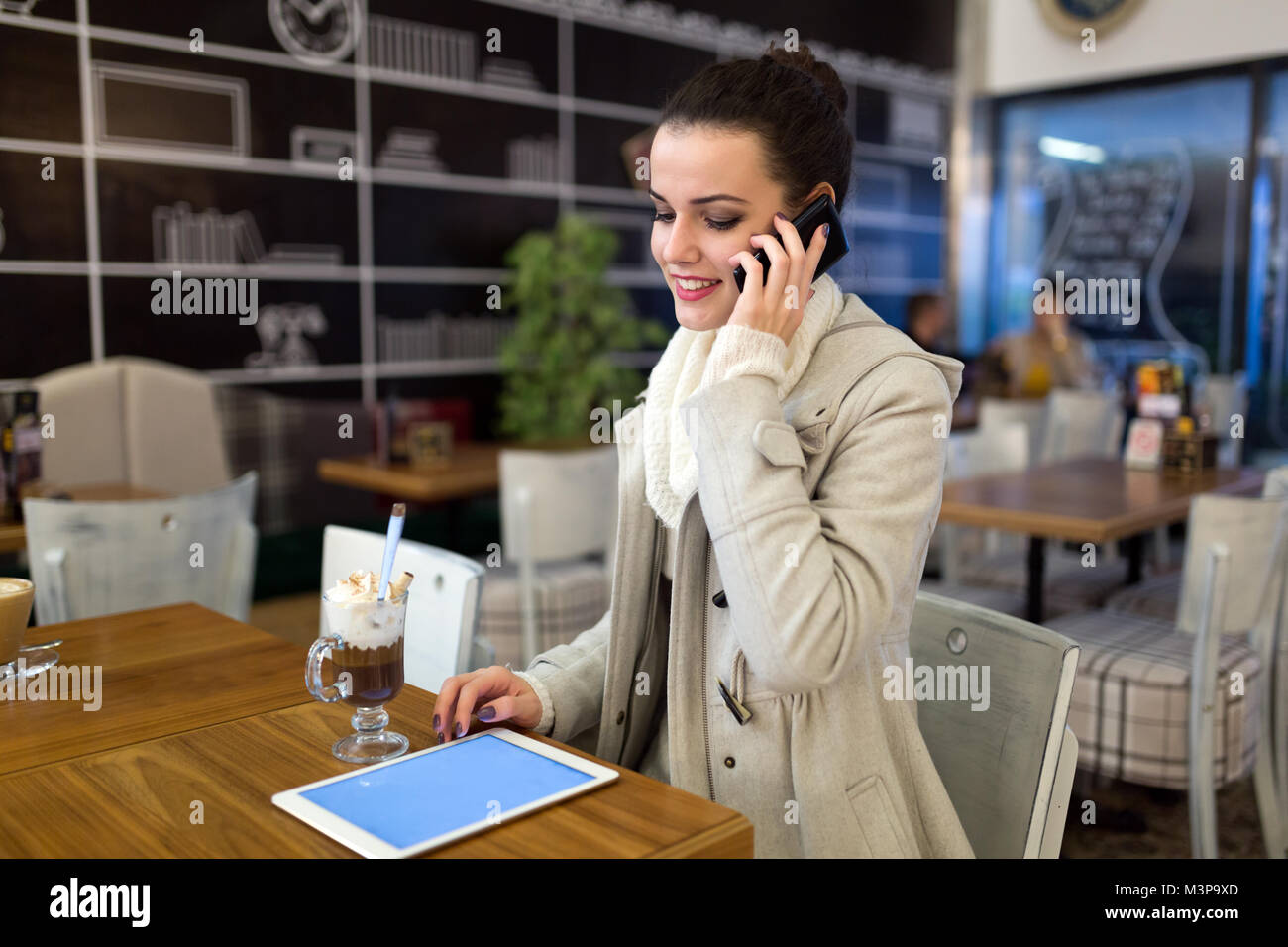 Attractive young woman using tablet in cafe - Stock Image
