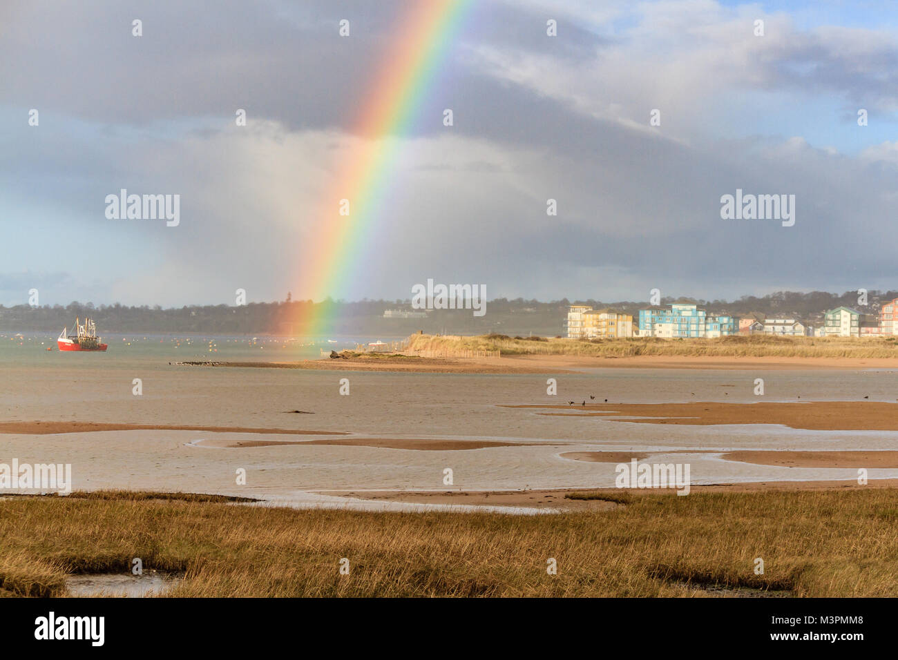 A rainbow forms after a brief shower ahead of heavy rain and strong winds forecast for throughout the night, from - Stock Image