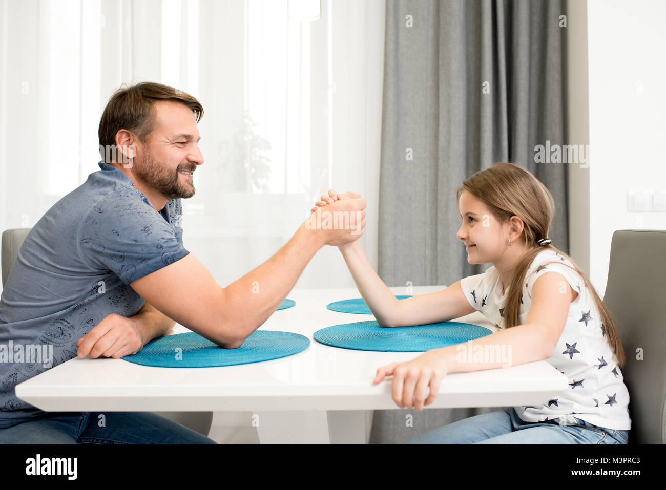 Father and Daughter Armwrestling - Stock Image