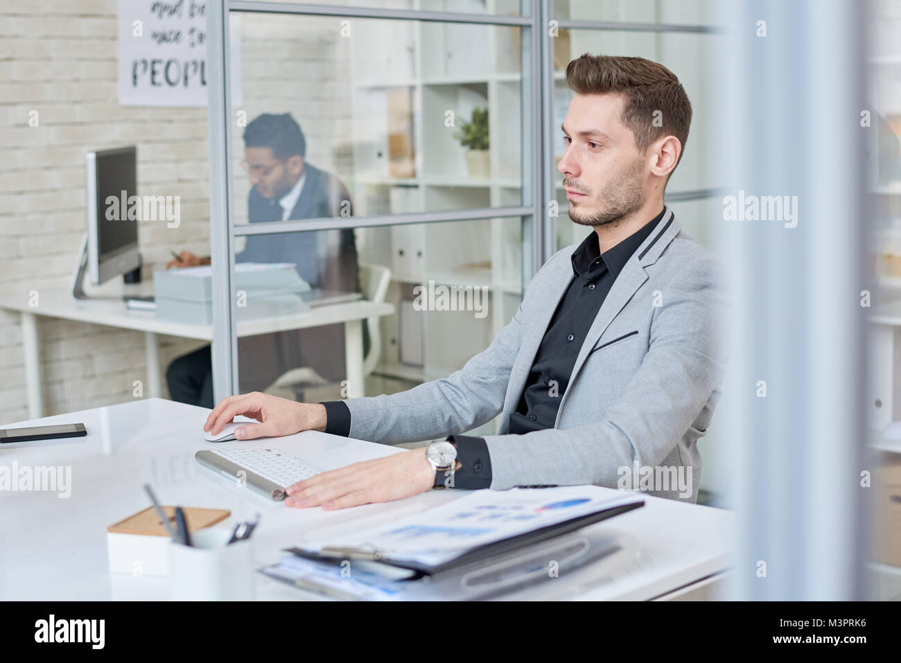 Young Businessman Working in Cubicle - Stock Image