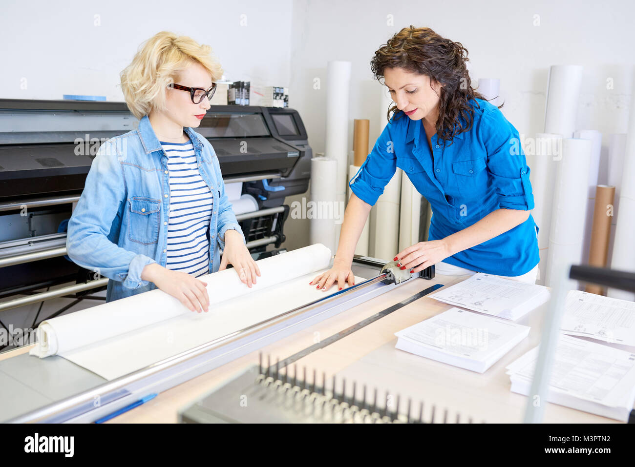 Women Cutting Paper in Printing Shop - Stock Image