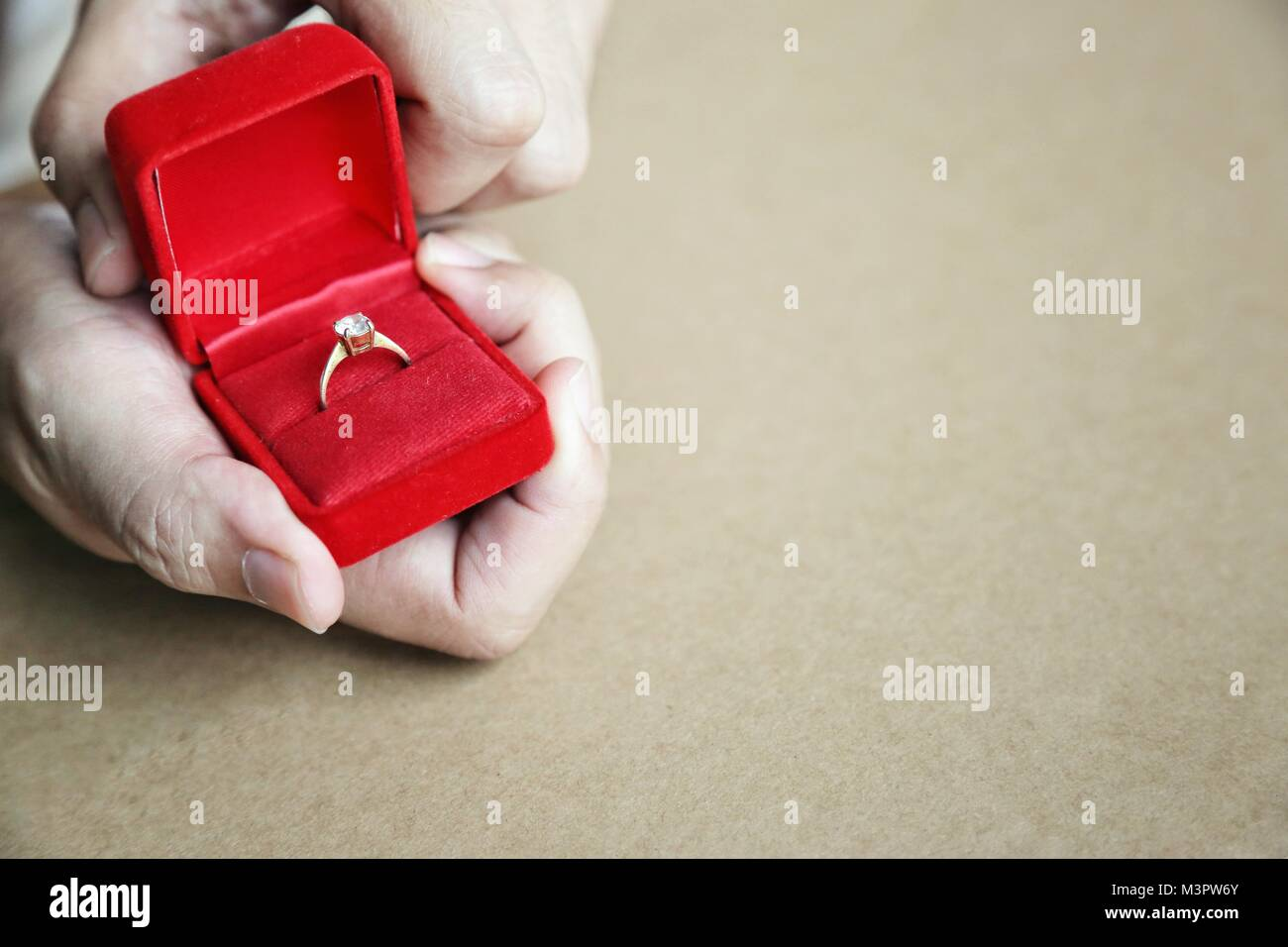 Red gift box opened with diamond ring in mans hands. Concept of the engagement ring, Valentine surprise gift, symbol - Stock Image