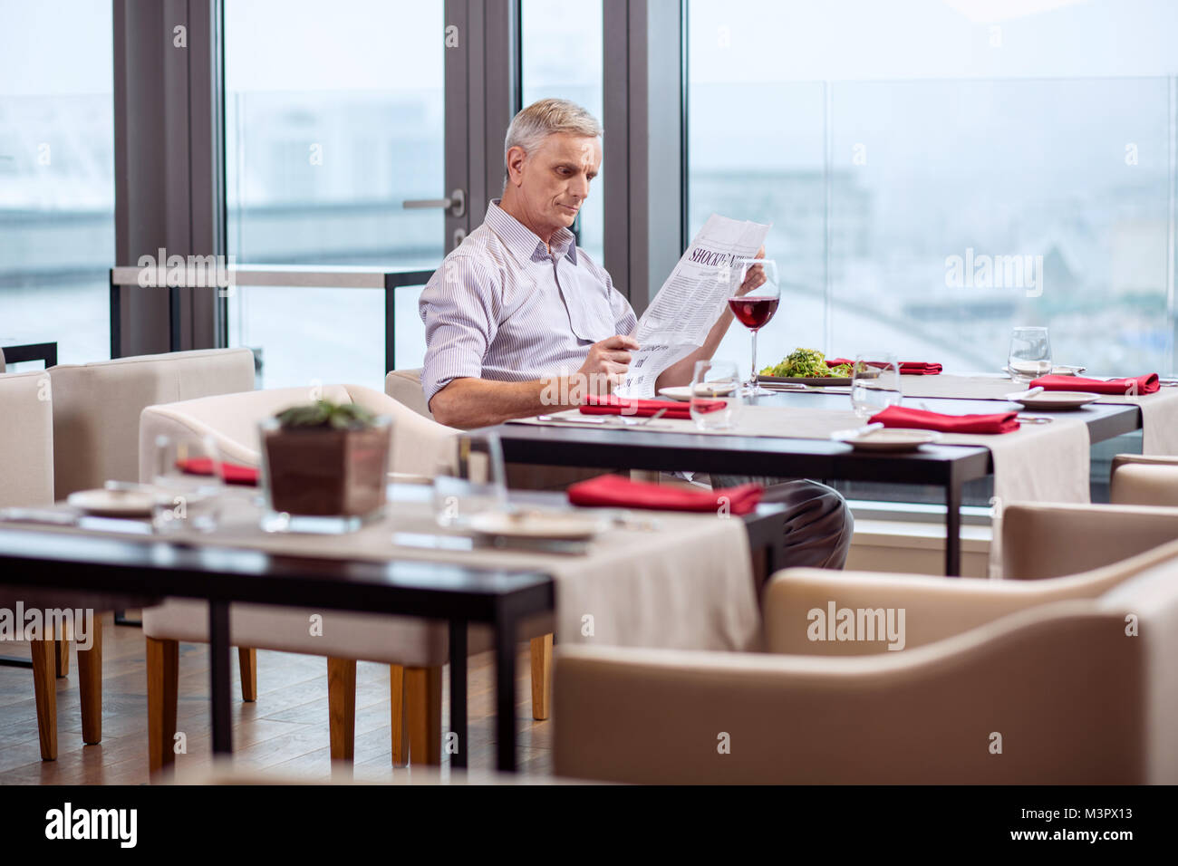 Musing mature man studying news - Stock Image
