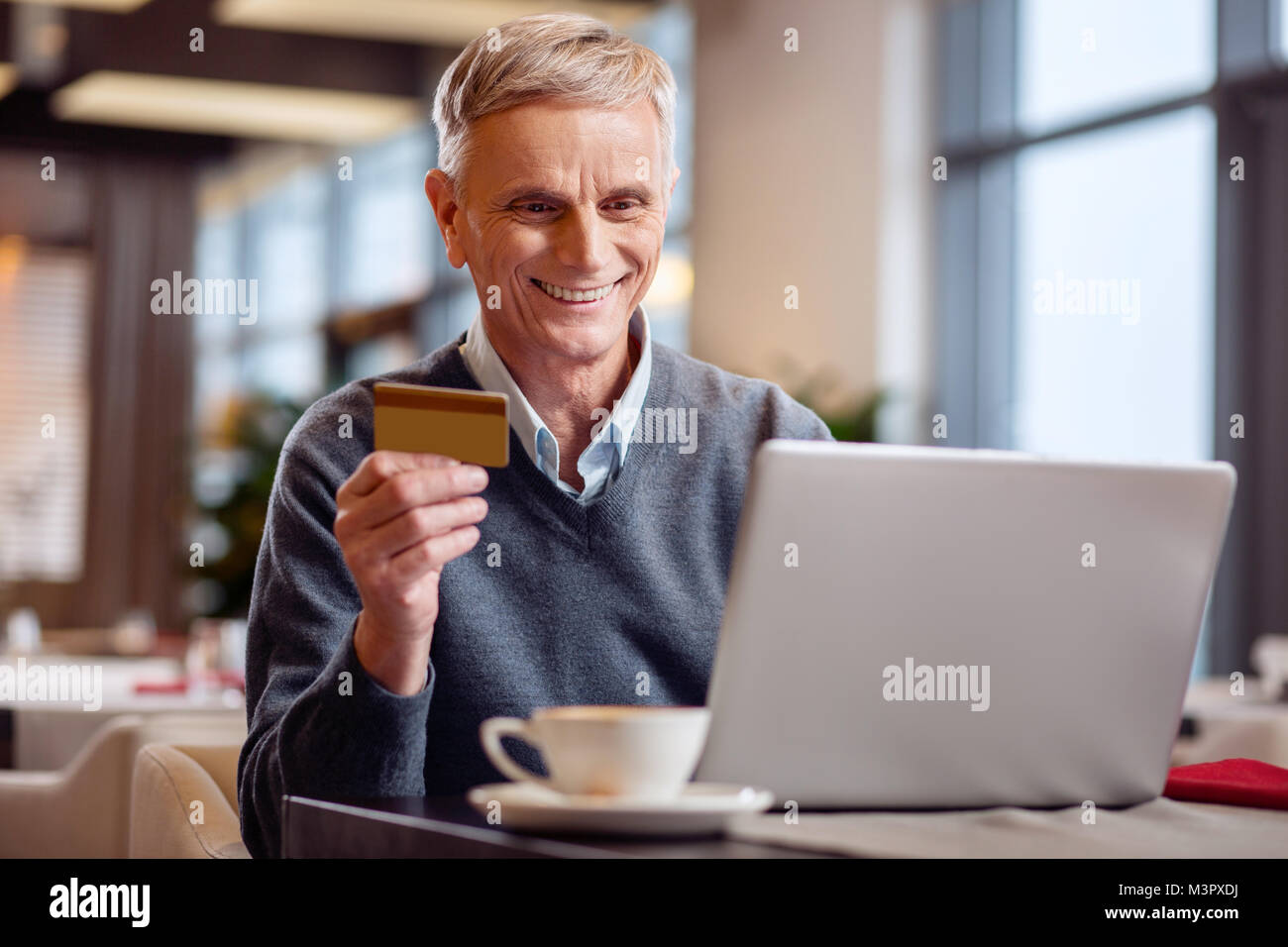 Happy mature man paying online - Stock Image
