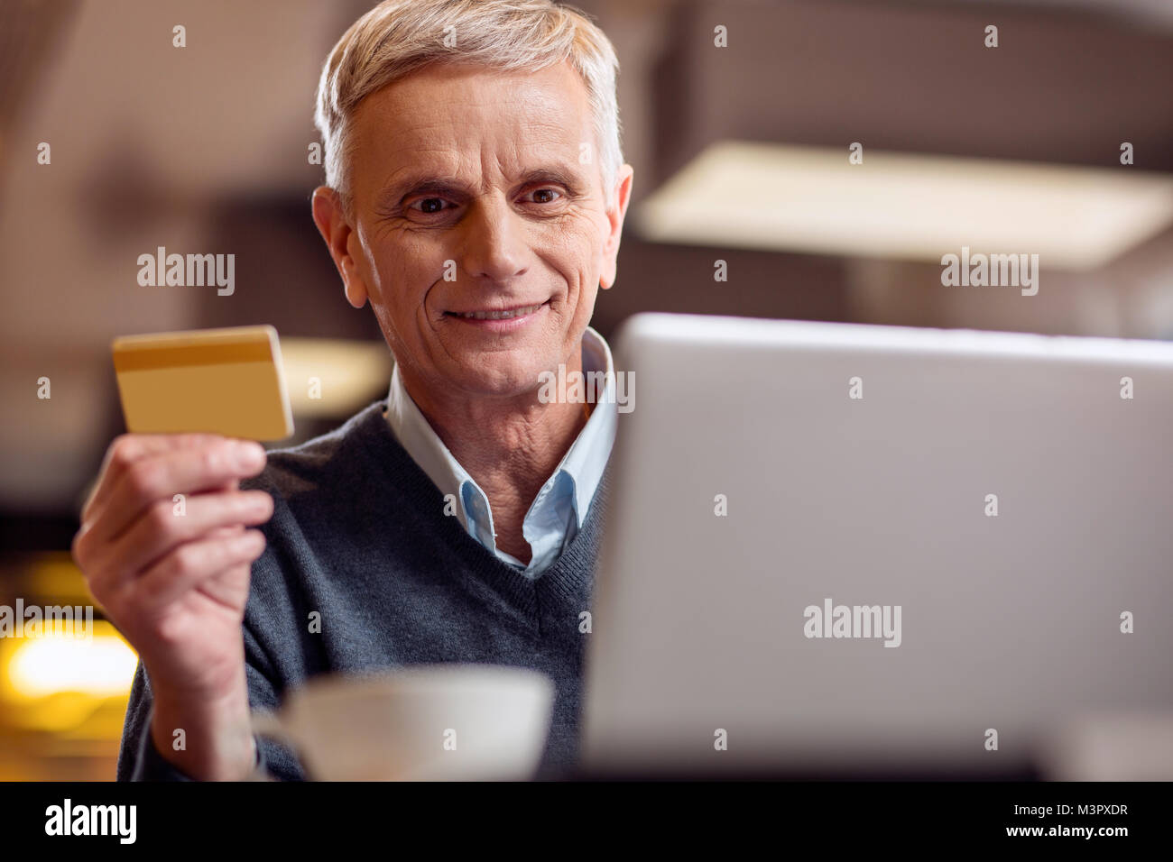 Cheerful mature man typing his card number - Stock Image