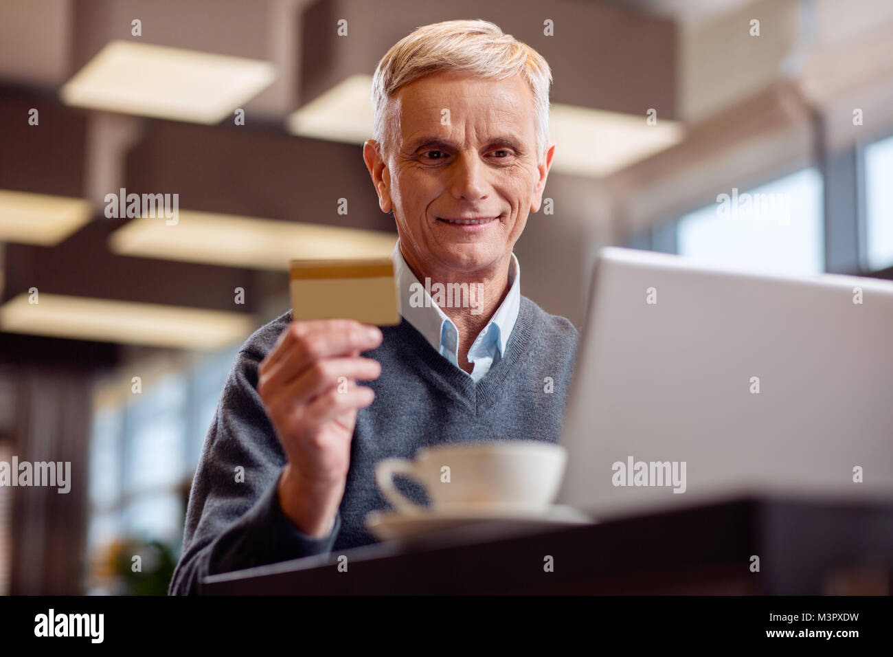 Energetic mature man paying with card - Stock Image