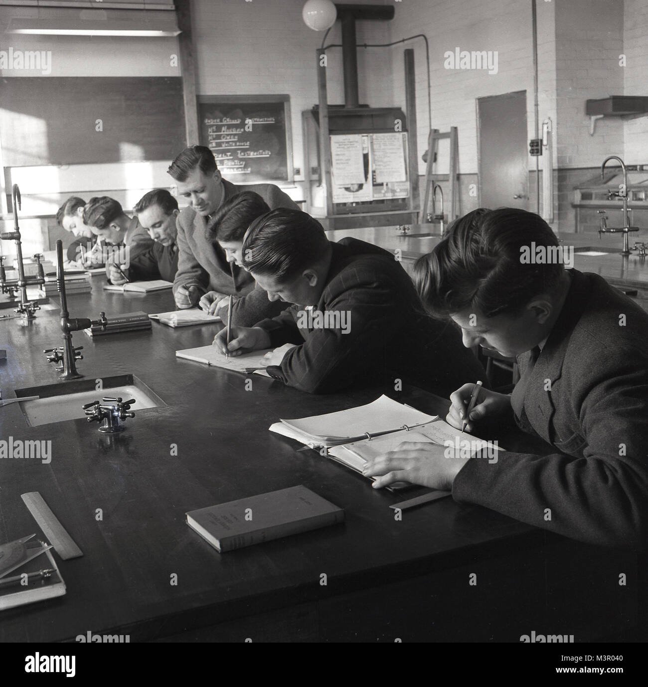 1950s, historical, young male science students sitting at a work bench in a laboratory at a technical college writing - Stock Image