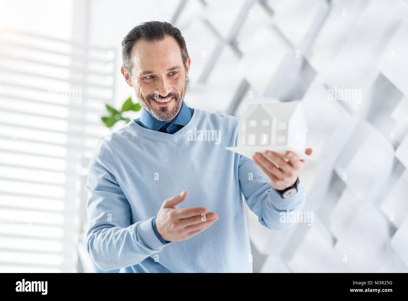 Inspired architect holding a model of a house - Stock Image