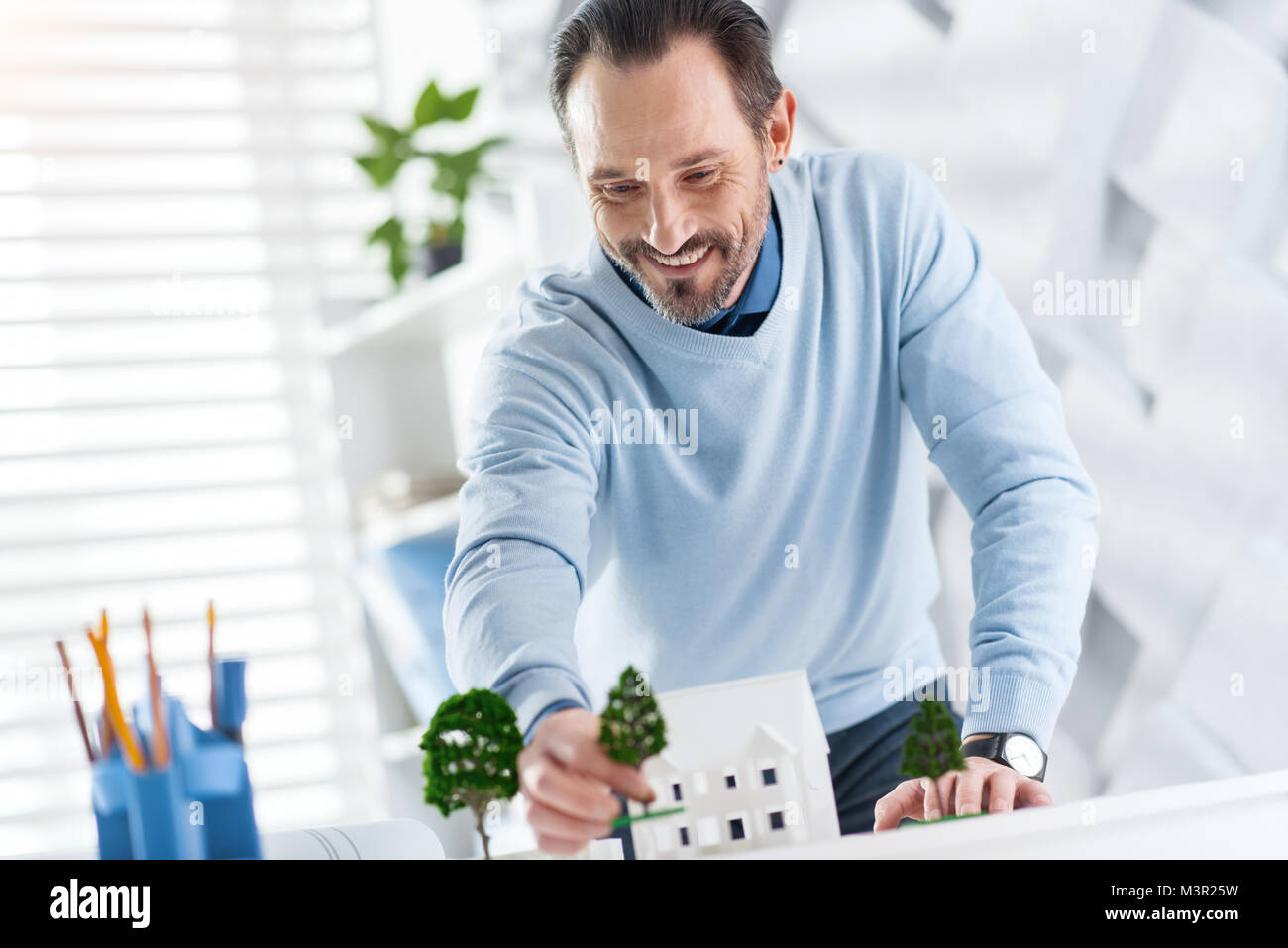 Joyful architect constructing the model of a house - Stock Image