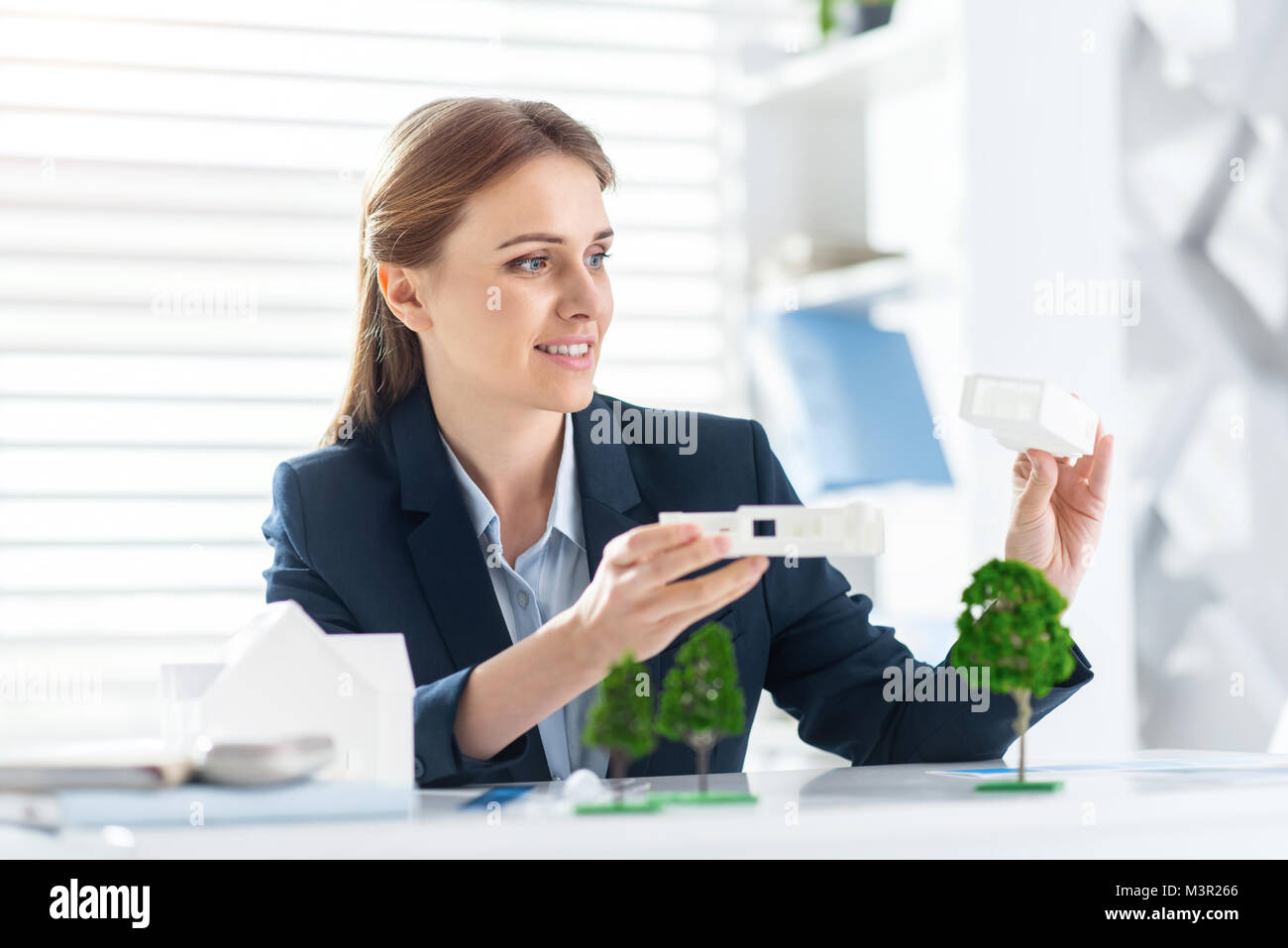 Happy engineer holding the models of the house - Stock Image