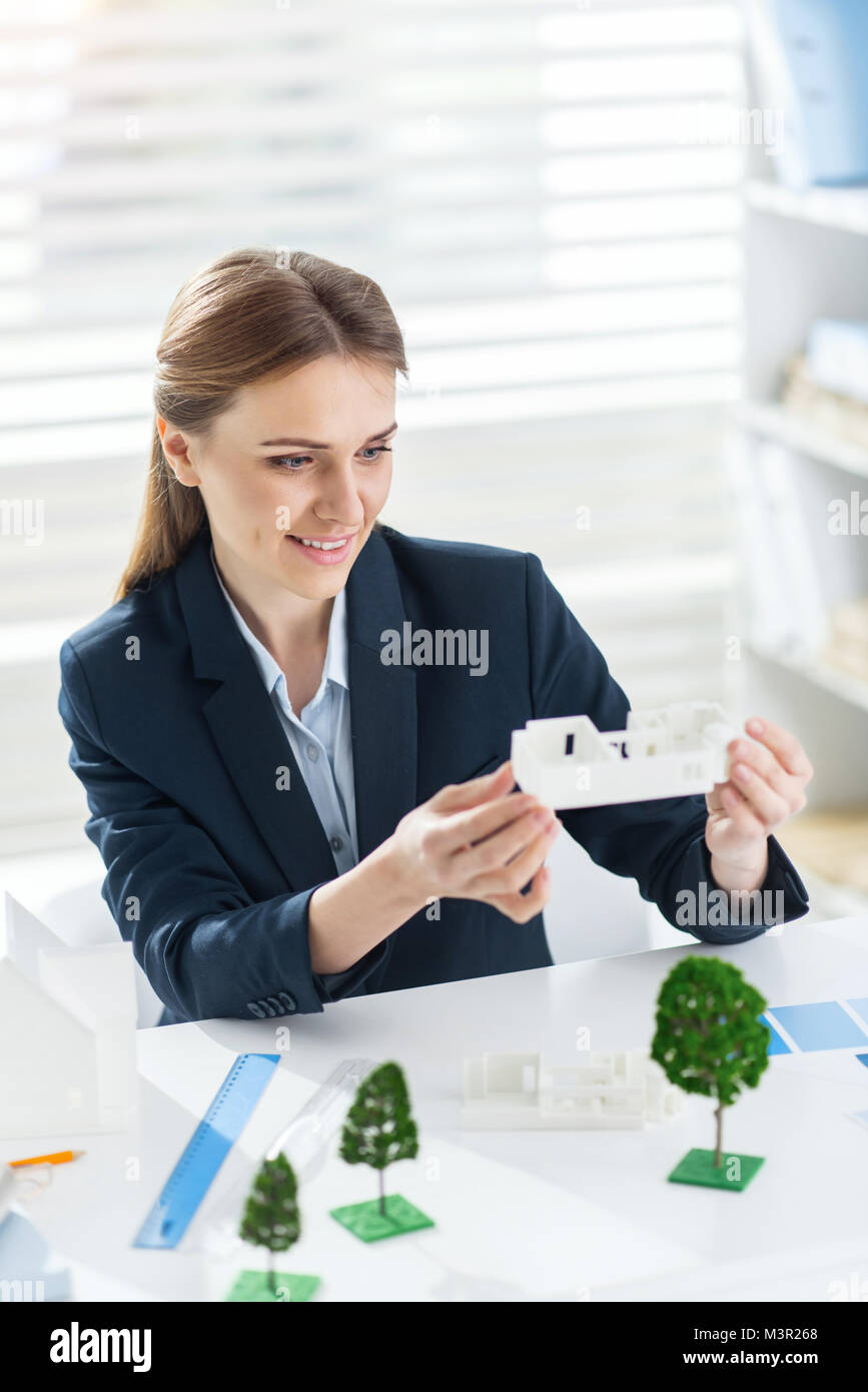 Alert engineer holding the models of the house - Stock Image