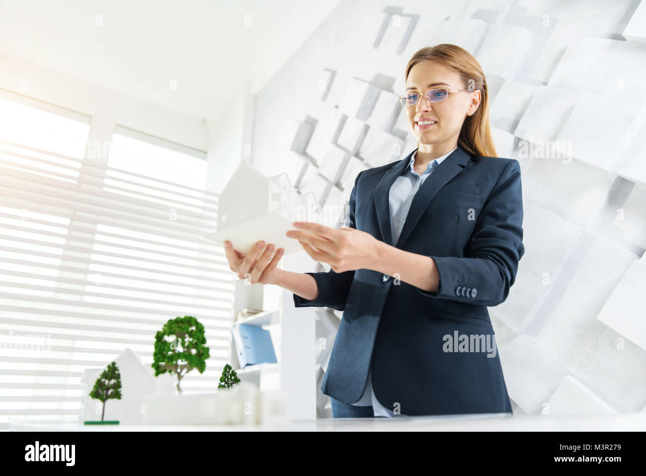 Glad engineer standing at the table with a little house - Stock Image