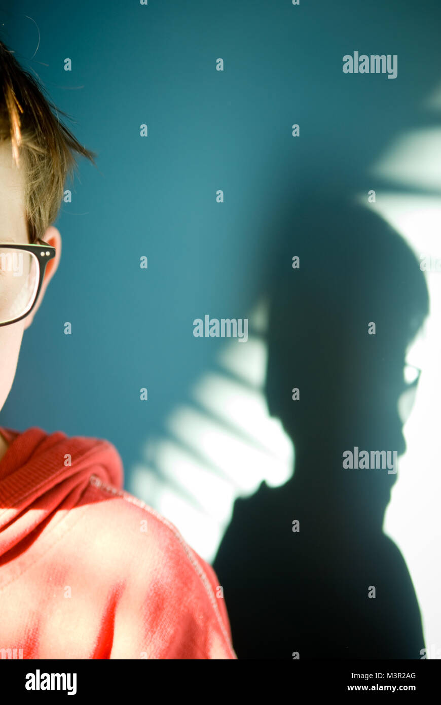 moody and atmospheric cropped view of ten year old boy face wearing glasses with his shadow falling across a brightly - Stock Image
