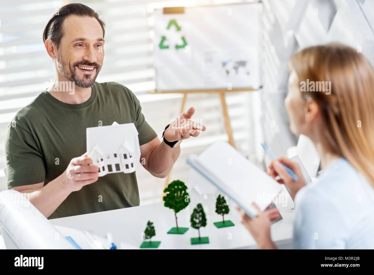 Happy man discussing eco-friendly project with his colleague - Stock Image