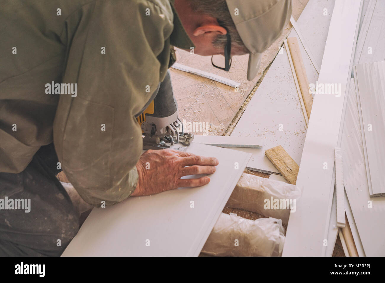 The builder works with white plastic parts - Stock Image