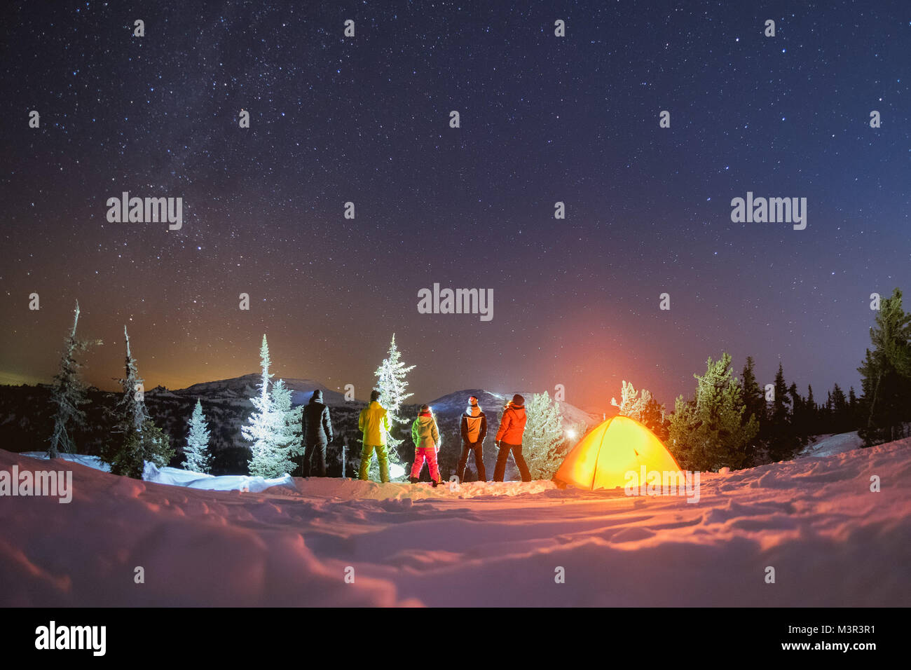 Travel night camping winter concept with friends and tent Stock Photo