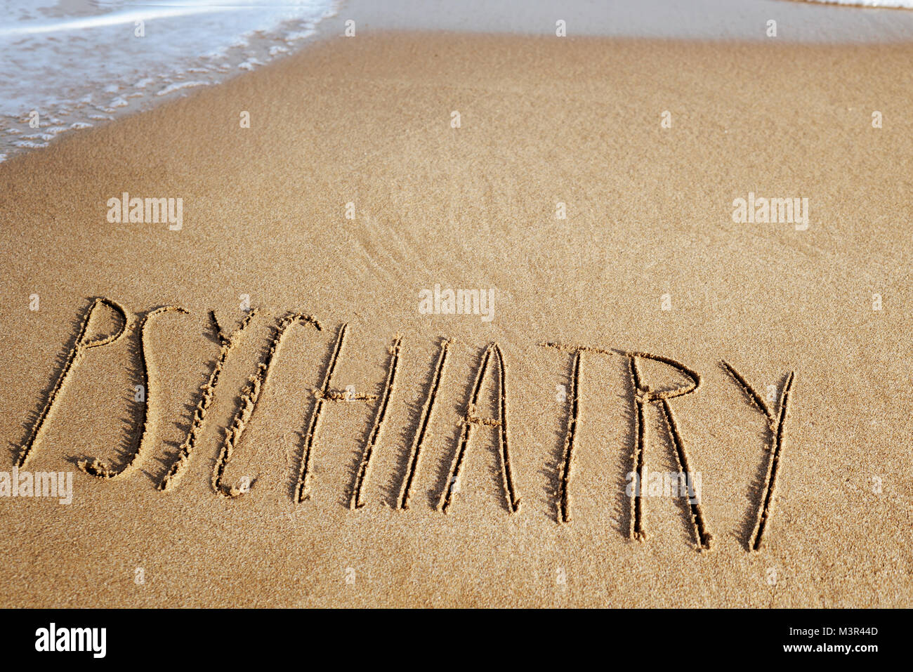 the word psychiatry written in the sand of a beach, with sea foam on the left and some blank space on top - Stock Image