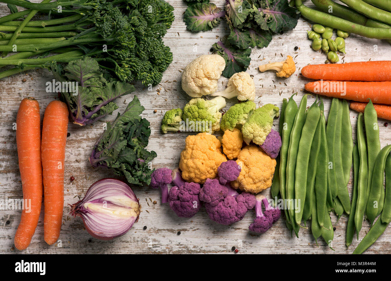 high angle shot of some different raw vegetables, such as cauliflower of different colors, broccolini, fava beans, - Stock Image