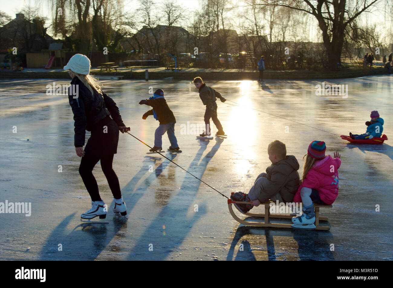 Young mother with children pulling a sled and skating on ice together in the Netherlands - Stock Image