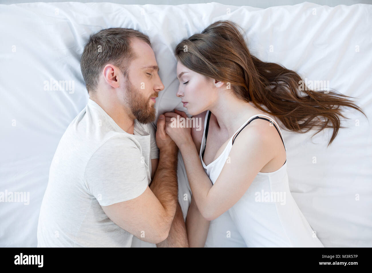 Happy couple sleeping together and holding hands - Stock Image