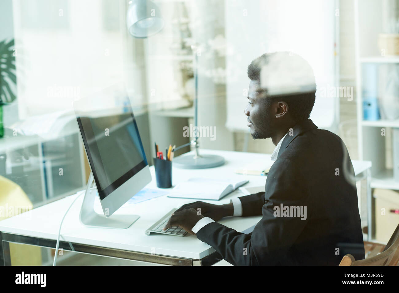 Successful African Businessman using PC - Stock Image