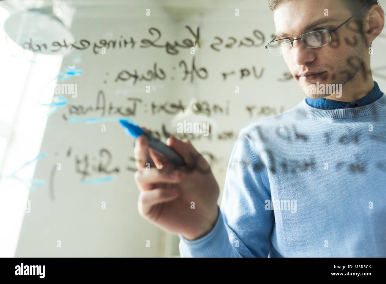 Young IT Professional Writing on Glass Wall - Stock Image