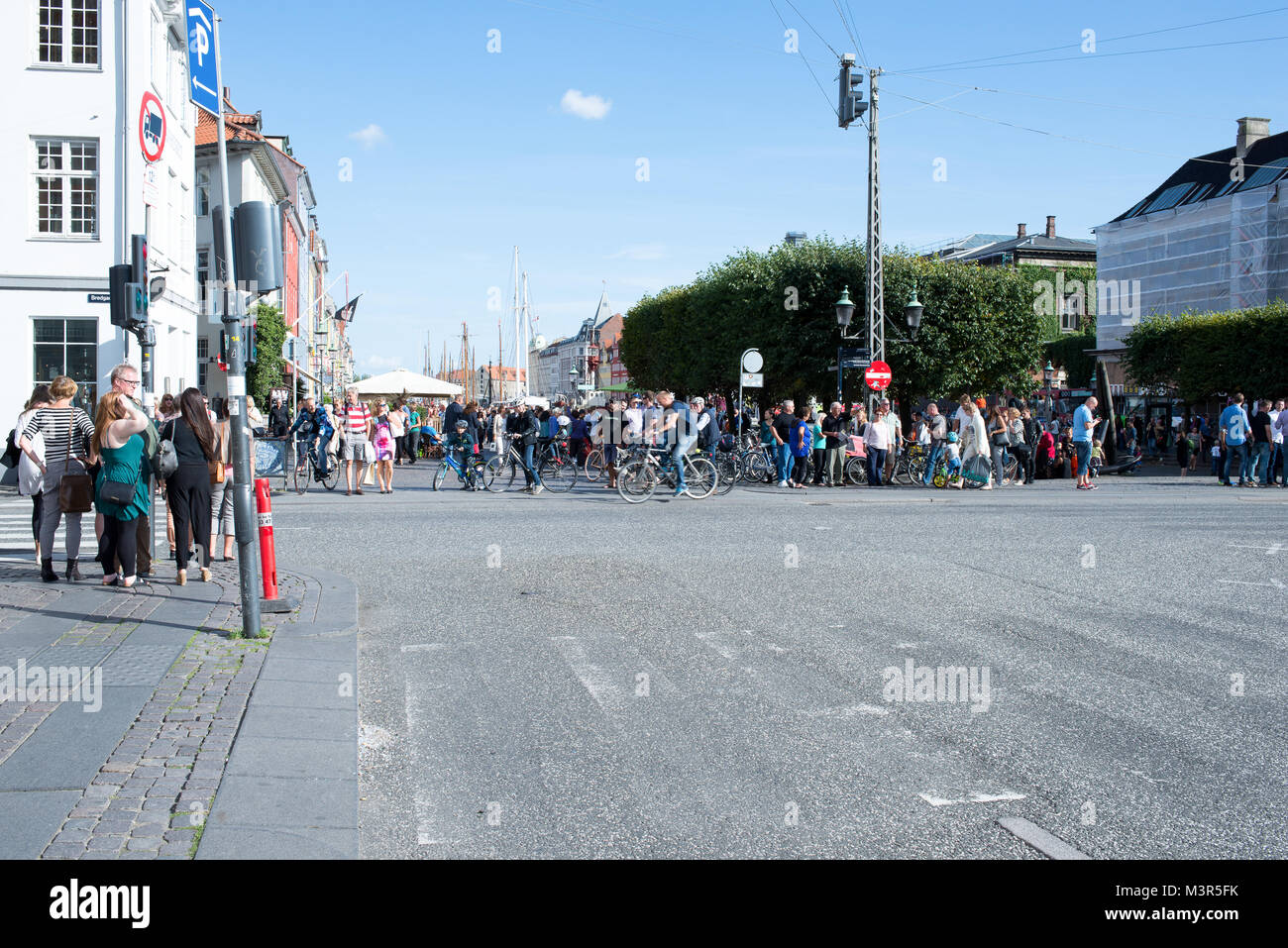 Crossing at Kongens Nytorv and Nyhavn in Copenhagen on a summer day with many cyclists and tourists - Stock Image