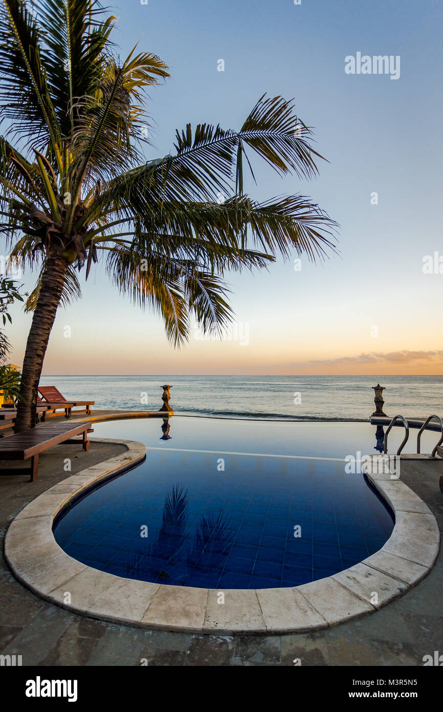 A Balinese infinity pool overlooking the Indian Ocean during a glorious sunset. Stock Photo