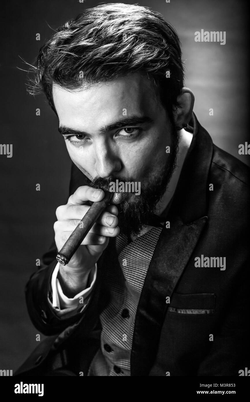 black and white portrait of bearded smoking cigar gentleman in a suit perceptive looking at the viewer - Stock Image