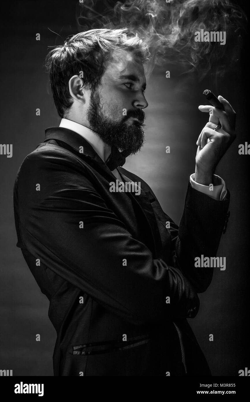 black and white portrait of bearded smoking gentleman in a suit perceptive looking at the cigar - Stock Image