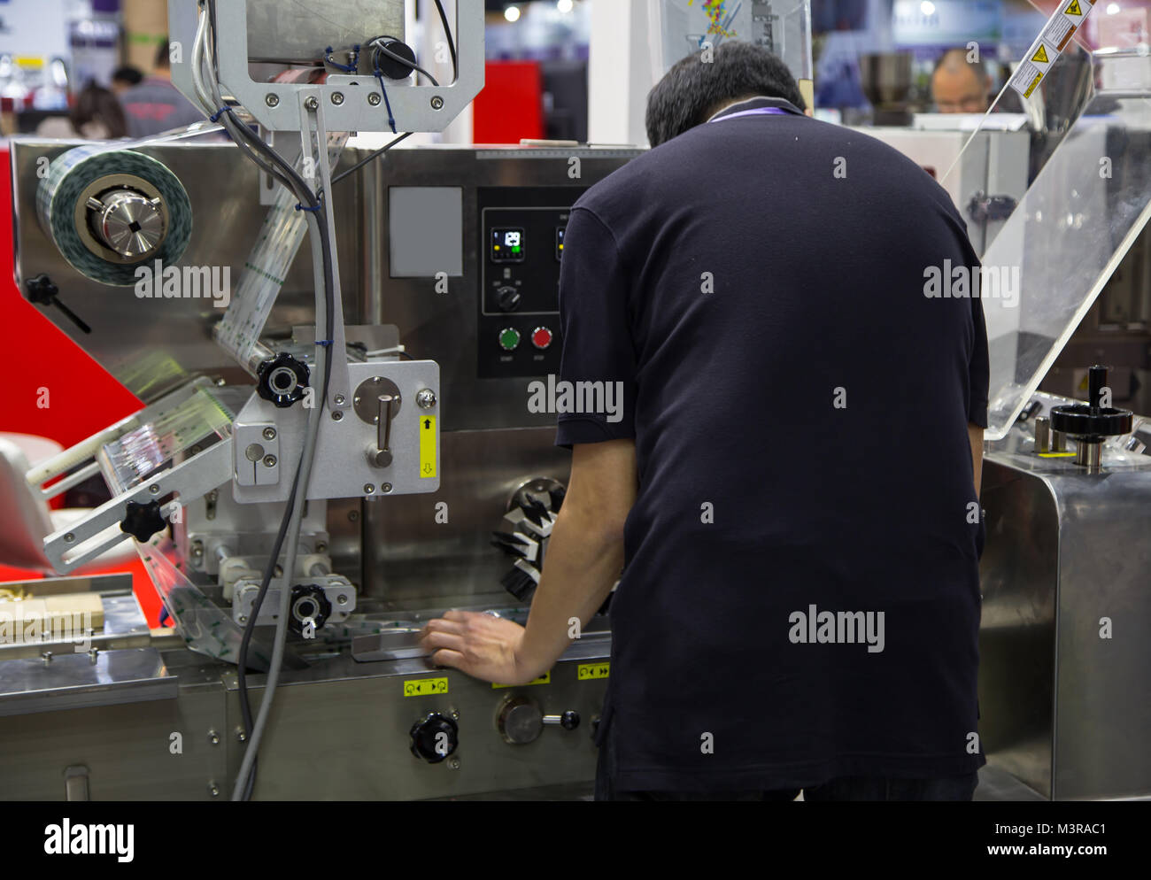 Food worker operate food packing machine - Stock Image
