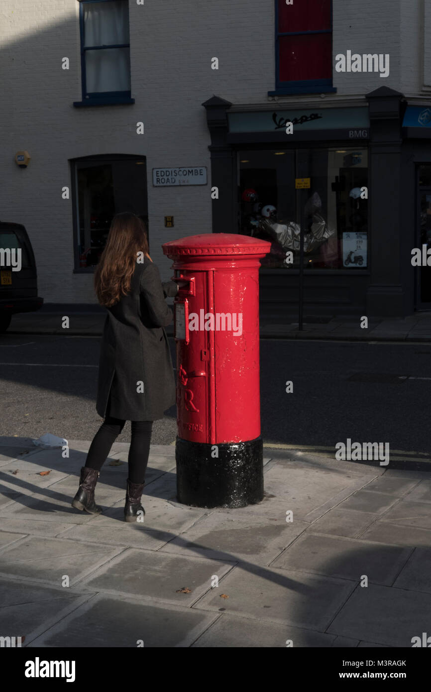 Young woman posting  a letter into a Red Royal Mail Box,Parsons Green,London,UK - Stock Image