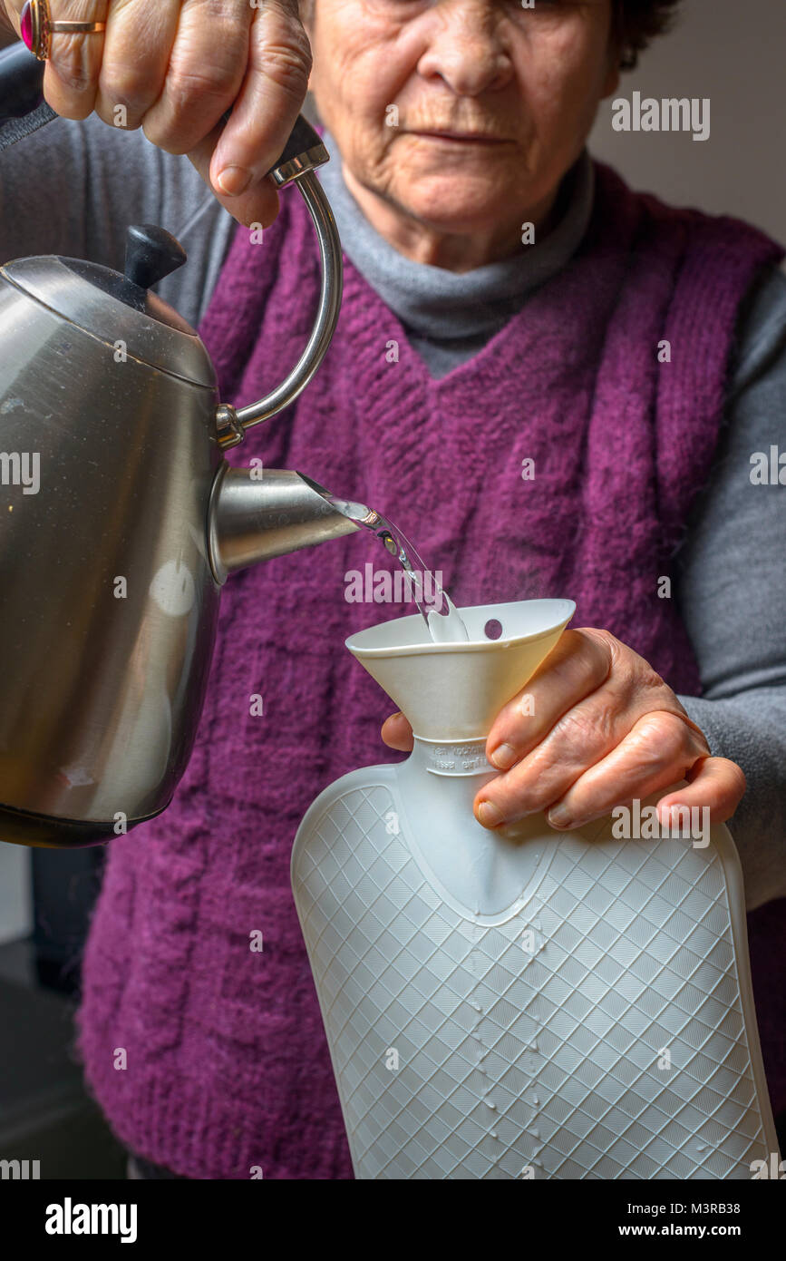 Senior woman fills hot water bottle,UK - Stock Image