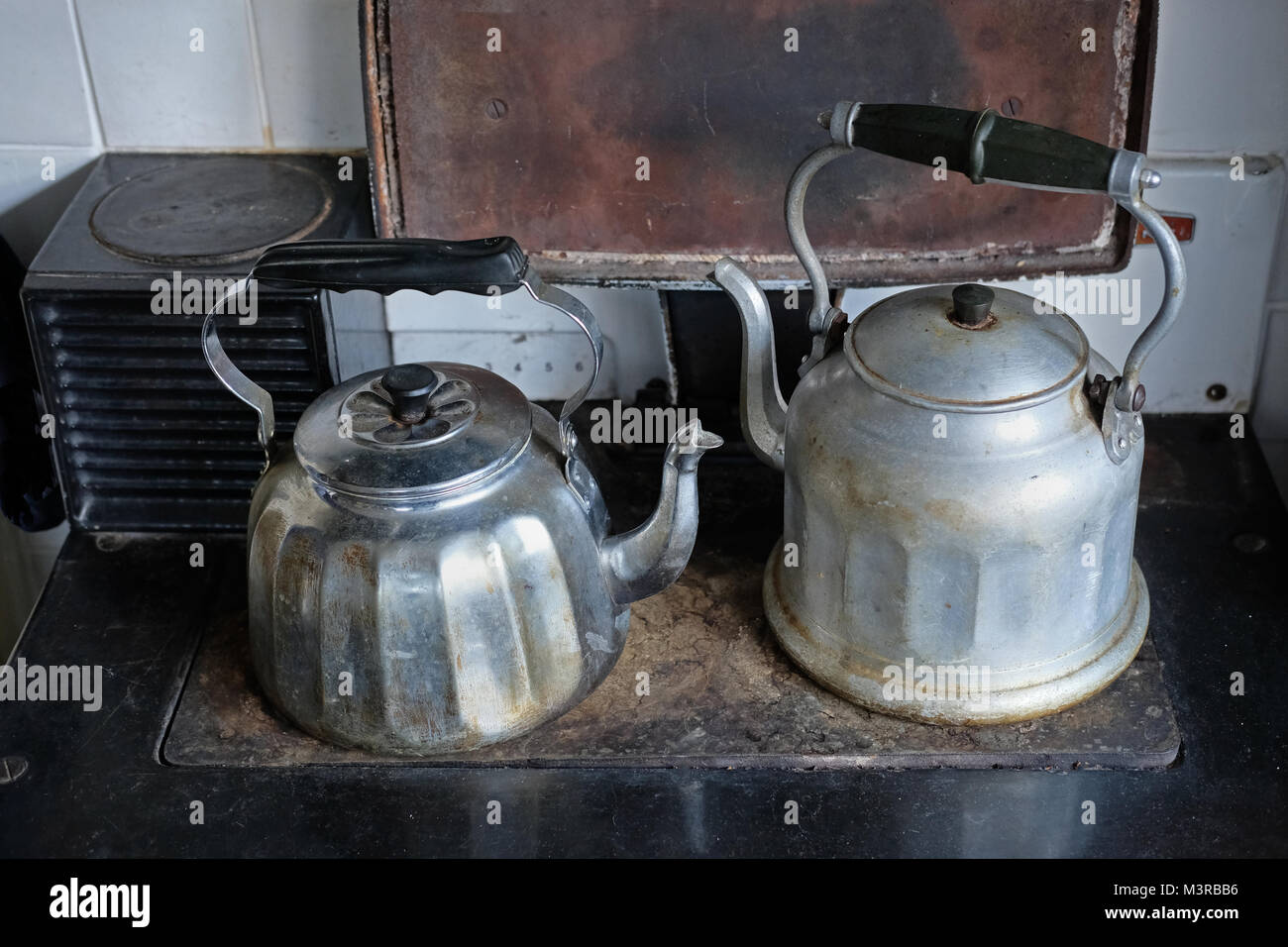Two kettles on an old oil-fired range. - Stock Image