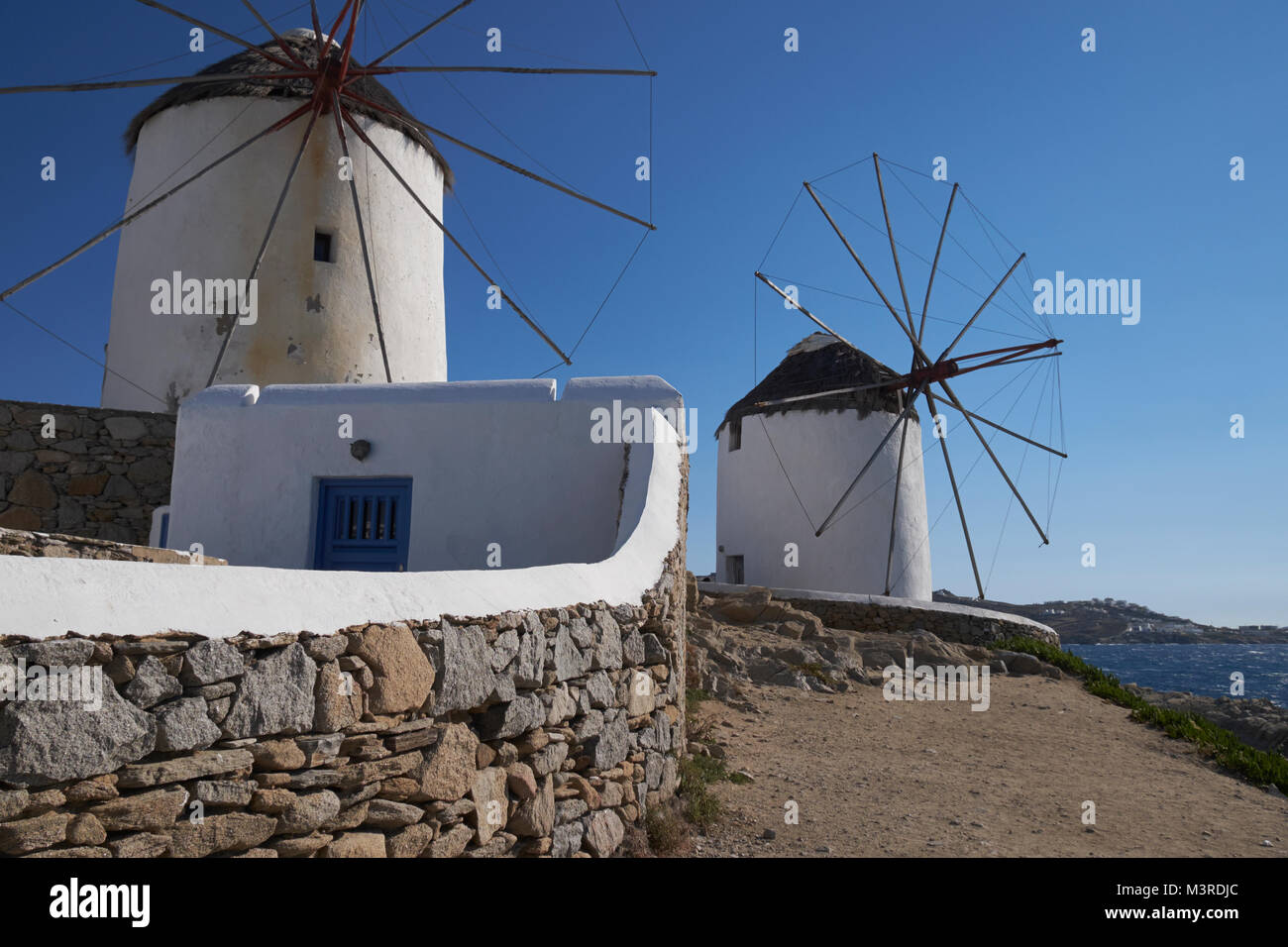 Iconic windmills overlooking the town of Mykonos (Chora), Cyclades Islands, Aegean Sea, Greece. Stock Photo