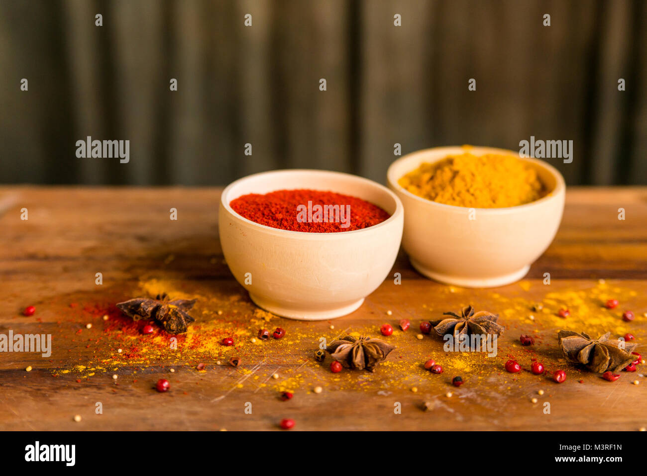 Two wooden bowls with paprika and turmeric powder - Stock Image