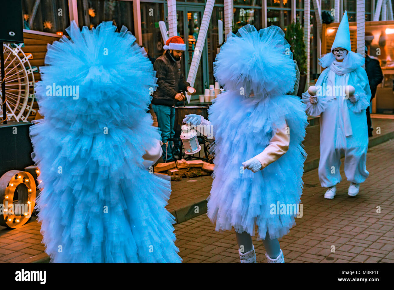 People in fluffy blue costumes in street - Stock Image