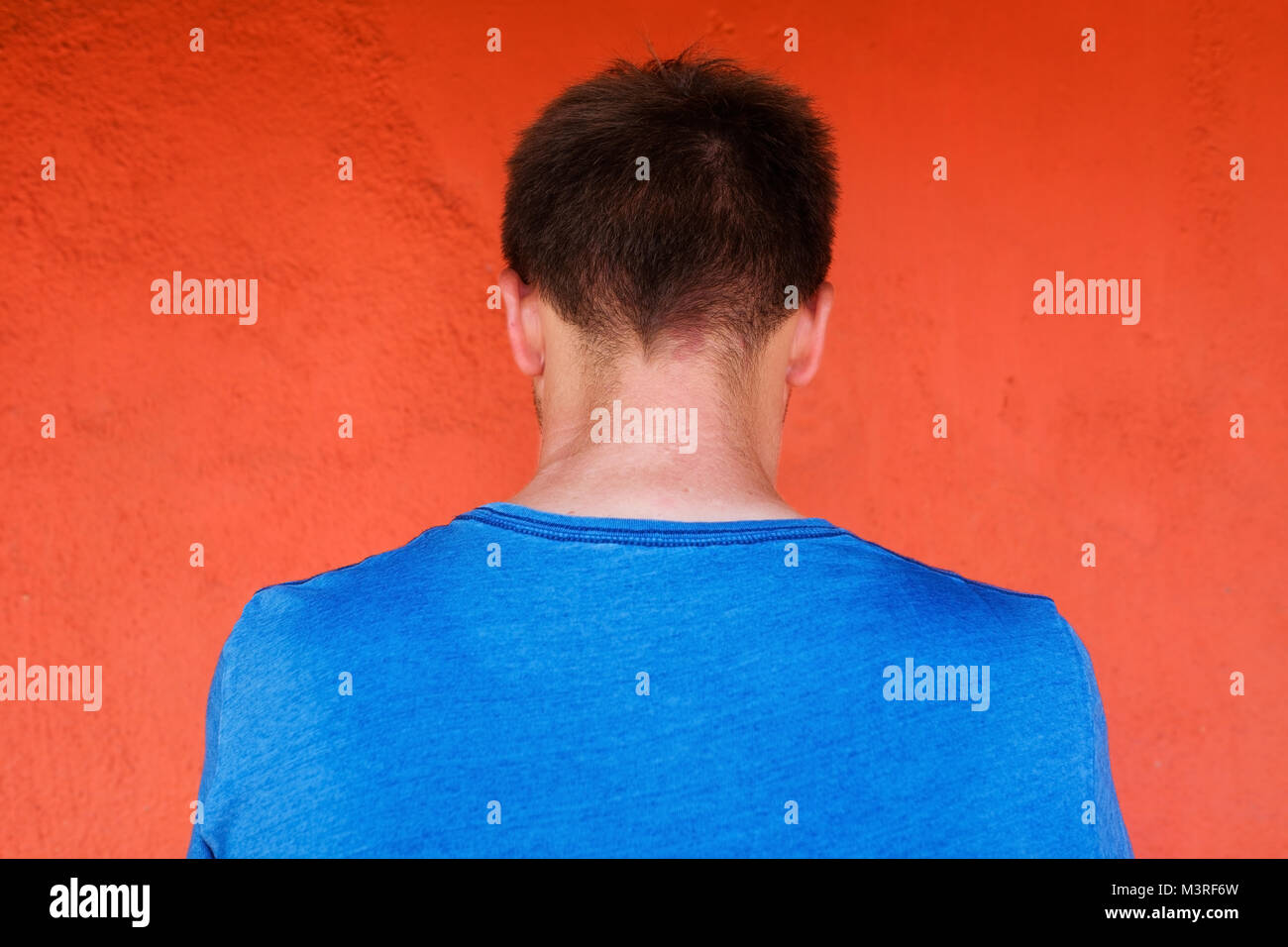 Back pose, photo of young man looks ahead. He feels shame. He is alone and hide his face. - Stock Image