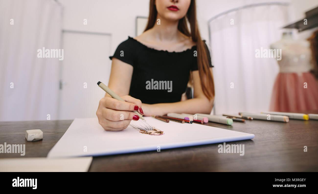 Female fashion entrepreneur sketching a design sitting at her table. Cropped shot fashion designer making a drawing - Stock Image